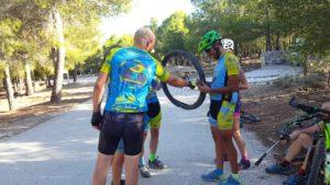 Mecánicos en ruta arreglando pinchazo de bicicleta de Toñi en sierra Muela Albudeite por Comunidad Biker MTB
