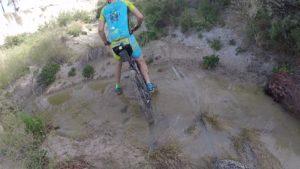 Ciclista de montaña y comunitario Kronxito metiendo la pierna en el barro del río Chícamo en Abanilla por Comunidad Biker MTB