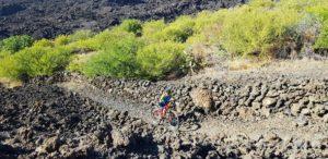 Empujando la bicicleta de montaña por la Montaña Negra de piedras volcánicas en Tenerife por Comunidad Biker MTB